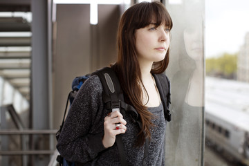 Young woman waiting in train station