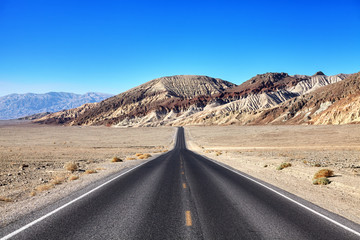 Desert road towards mountain range at Death Valley, travel concept, focus on mountains, USA.