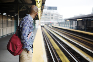 Young man waiting for arriving train on subway platform