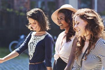 Three stylish female friends walking down street