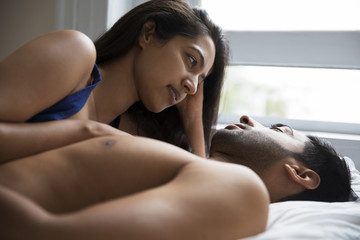 Indian couple lying together in bed