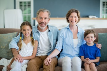 Portrait of smiling family sitting together on sofa
