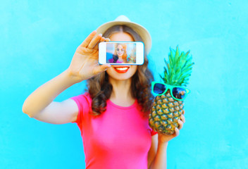 Fashion woman with pineapple taking picture self portrait on smartphone over colorful blue background screen closeup