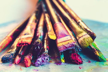Artist paintbrushes with paint closeup on artistic canvas. Retro toned.