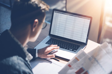 Closeup view of banking finance analyst in eyeglasses working at sunny office on laptop while sitting at wooden table.Businessman analyze stock report on notebook screen.Blurred background,horizontal.