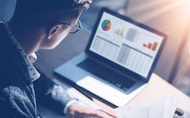 Closeup view of finance market analyst in eyeglasses working at sunny office on laptop while sitting at wooden table.Businessman analyze stock report on notebook screen.Blurred background,horizontal.