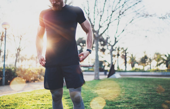 Workout lifestyle concept.Young man preparing muscles before training.Muscular athlete exercising outside in sunny park. Blurred background.