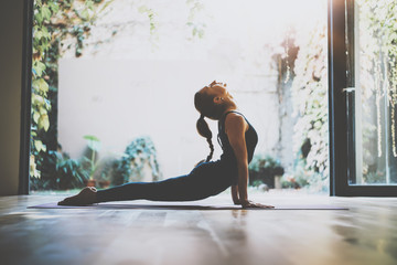 Portrait of gorgeous young woman practicing yoga indoor. Beautiful girl practice cobra asana in class.Calmness and relax, female happiness.Horizontal, blurred background.Visual effects. Wall mural