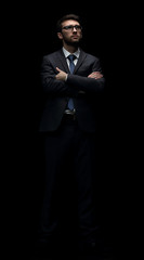 Young business man ,portrait isolated on black background.