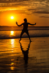Silhouette of young male capoeira dancer, yoga and martial art specialist at beach in Mexico during spectacular sunset