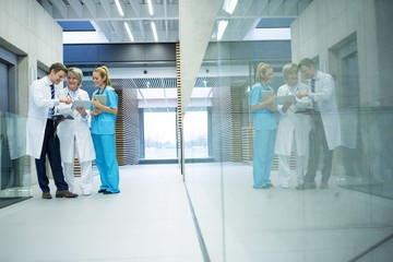 Medical team discussing over digital tablet in corridor