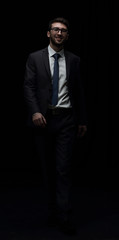 Young successful businessman in a  suit is moving forward isolat