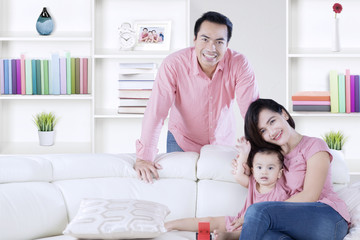 Parents play with their daughter at home