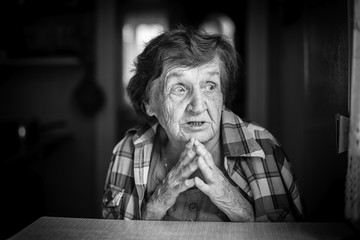 Emotional portrait of an elderly woman. Black and white photo.