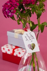 Close-up of happy mothers day card on flowers vase