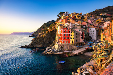 Riomaggiore town, cape and sea landscape at sunset. Cinque Terre, Liguria, Italy