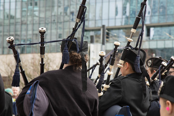 Teens playing bagpipes street background
