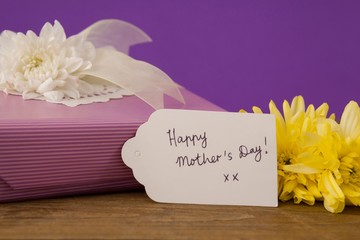 Happy mothers day card on gift box with flowers