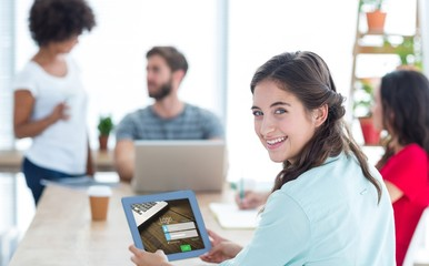 Composite image of smiling businesswoman using tablet