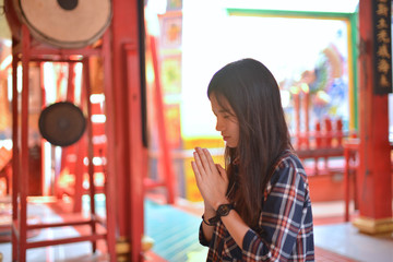 Asian woman prays respect to Chinese buddha in Chinese temple