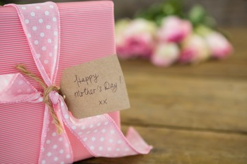 Gift box with happy mother day tag on wooden surface