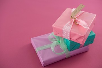 Gift boxes with happy mother day tag against pink background