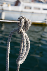 White rope, canat knotted in a knot hanging on a board yacht, sailboat