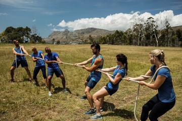 Foto op Canvas Fietsen People playing tug of war during obstacle training course