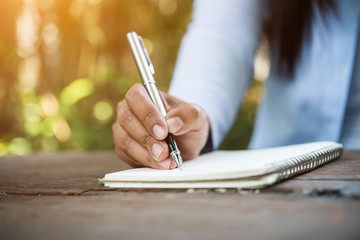 Woman writing something on notebook