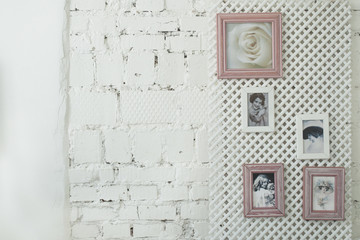 Framed vintage photos on a white brick wall