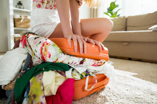 Happy young woman in colorful summer outfit sitting on orange staffed suitcase, smiling. Top shot. Girl packing bag  for travel, closing hardly overflowing luggage bag.