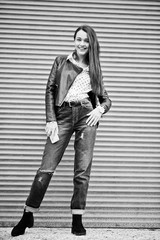 Portrait of stylish young girl wear on leather jacket and ripped jeans with mobile phone at hand background shutter texture. Street fashion model style. Black and white photo.