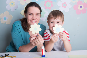 Child boy with mother have a fun cutting out scissors paper in the home. Preparation of a decor for Easter.  children's creativity..