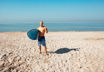 Surfer is going to surf in the ocean in a sunny day