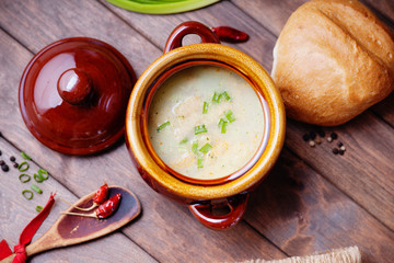 Cheese soup, bread bun and wooden spoon