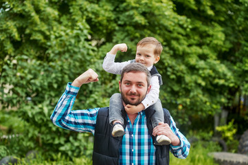 son sitting on the shoulders of the father , and show his muscles