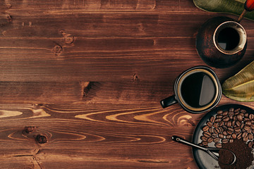 Hot coffee in black cup with beans, dry leaves and turkish pot cezve with copy space on brown old wooden board background, top view. Rustic style.