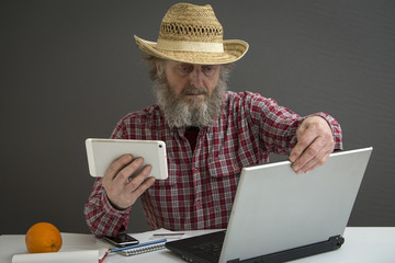 The farmer is at the computer.
