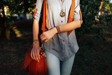A girl in the style of a hippie with a pendant and a handbag