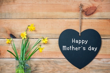 Happy mothers day card, wood planks with daffodils and a blackboard in the shape of a  heart