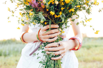 .A hippy girl holding a bouquet of wildflowers in her hands