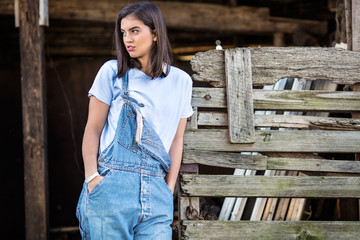Portrait of beautiful young farmer standing in front of the rustic wooden stable or barn