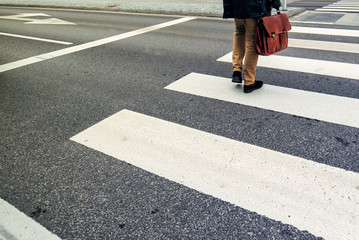 Businessman on pedestrian zebra crossing on his way to work