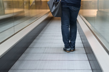 woman on the escalator rear view