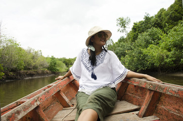 Traveller thai woman sit on service long tail boat for looking and travel view riverbank and Mangroves forest or Intertidal forest on river of Pak Nam Prasae
