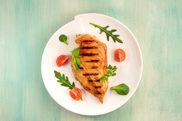 Grilled chicken fillet with cherry tomatoes and salad leaves