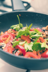 Mushrooms and fresh sweet red pepper in the pan for cooking. Spices and fresh parsley. Shallow depth of field. Toned