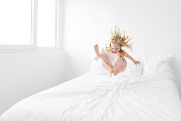little girl jumping on a white bed in mid-air