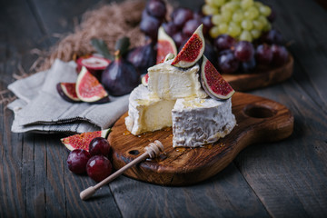 Homemade camembert cheese with fresh fruits on wooden board