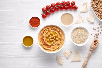 Bowl of hummus traditional arab healthy vegan dip chickpeas paste snack flat lay with natural ingridients, tahini, paprika, olive oil, pitta on table. Healthy vegetarian diet nutrition protein food